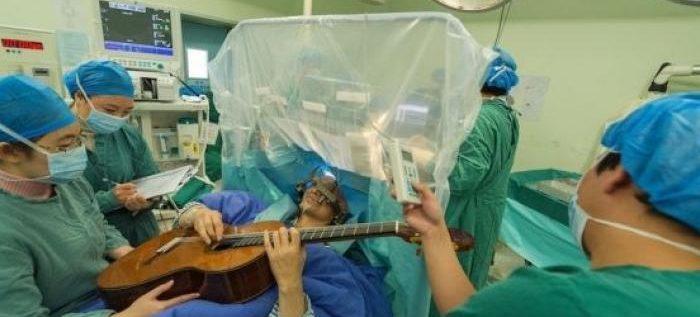 هندي يعزف الغيتار أثناء خضوعه لجراحة في المخ